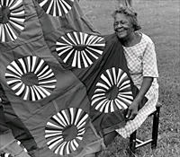 Fannie Lee Teals with her red, white and blue American Revolution Bicentennial quilt, 1977