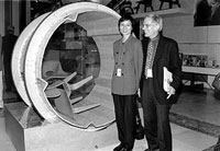 Eames exhibition designers Hsin-Ming Fung and Craig Hodgetts admire a tumbler designed to test the durability of the signature Eames molded plywood chairs.