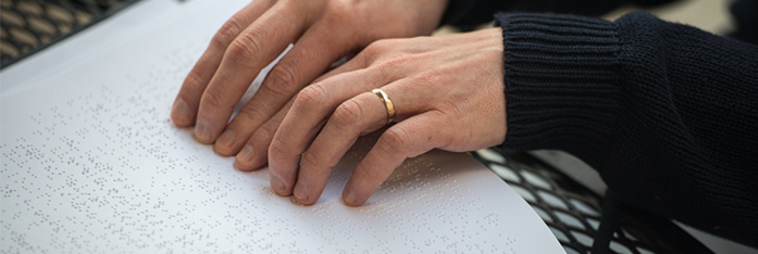 hands reading braille material from NLS Music collection
