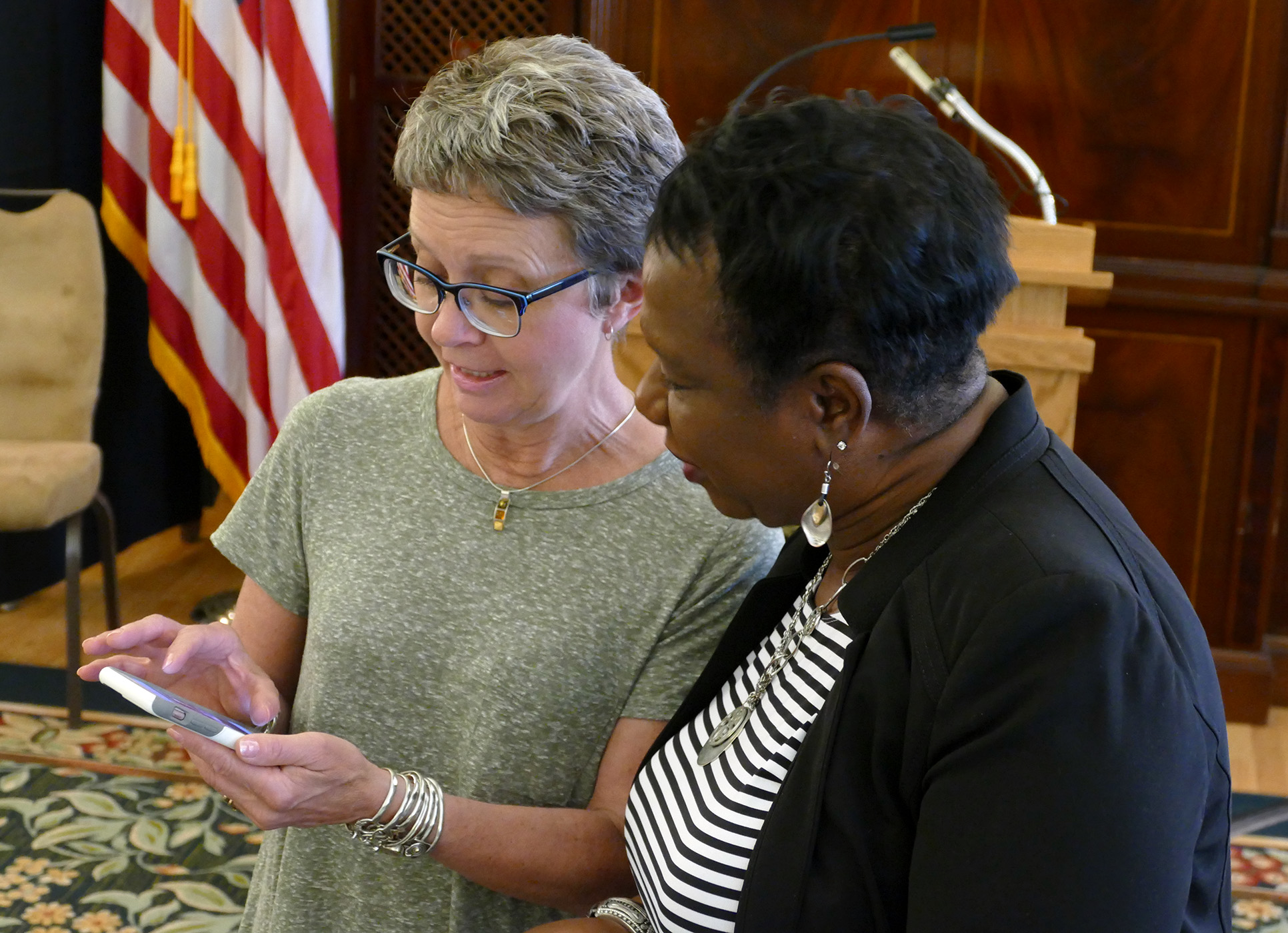 Two women look at a smartphone