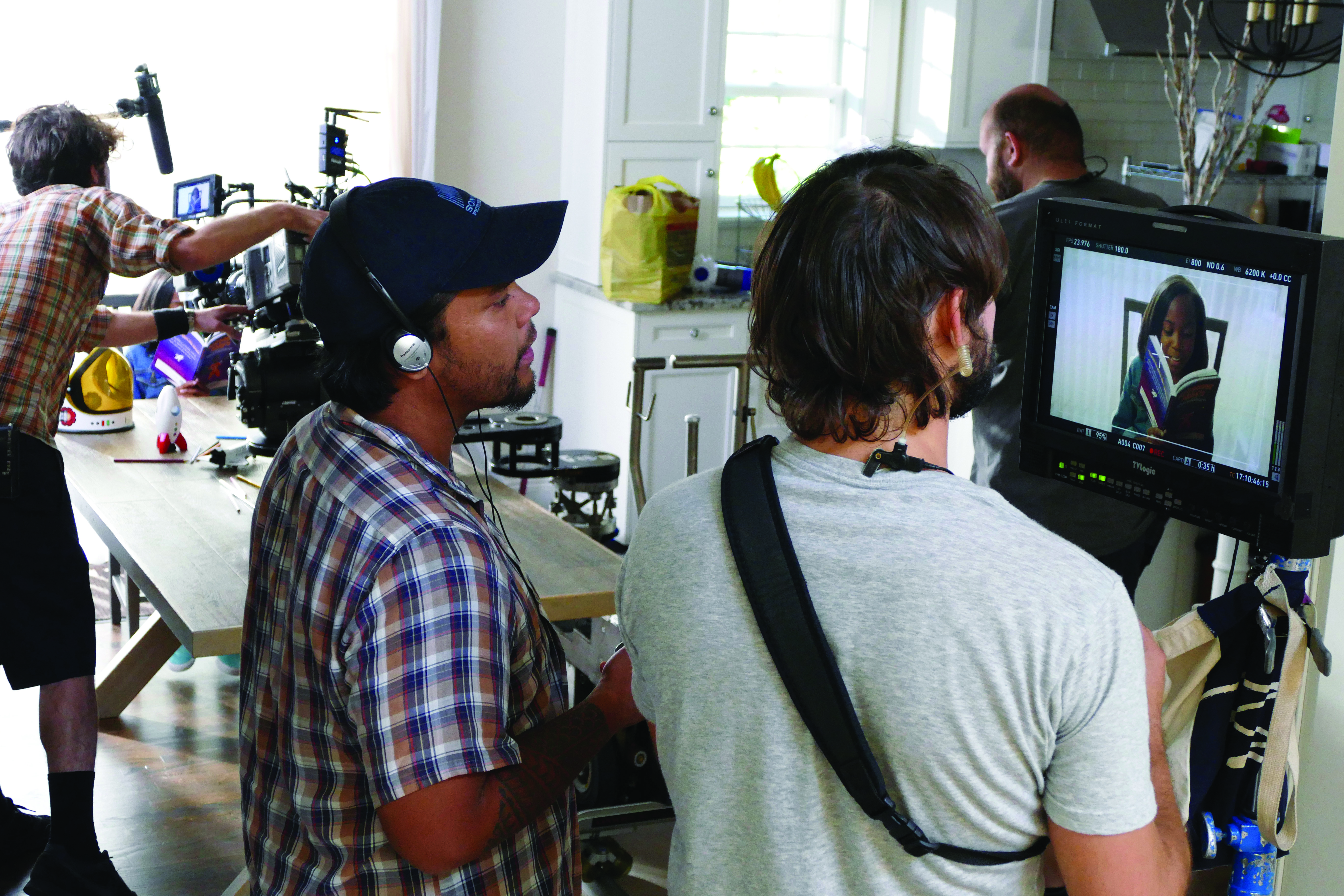 Director and crew member watch as the scene is being filmed nearby in the dining room.