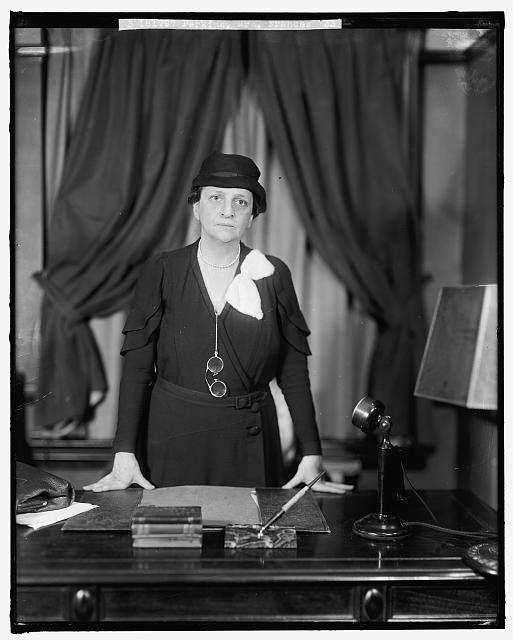 Portrait of Frances Perkins in her office, standing at her desk