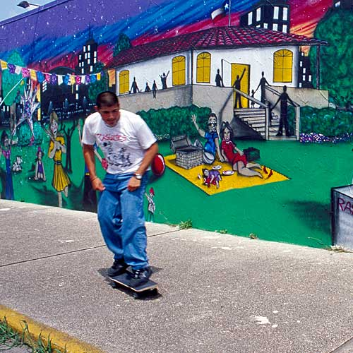 Skate Board Rider in Front of a Colorful Mural
