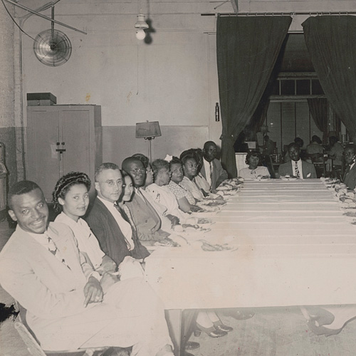 ['Rosa & Raymond Parks', 'seated at a banquet table', 'left side', 'third and fourth chair', 'likely at an NAACP branch meeting', 'Montgomery', 'Alabama']
