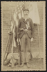 [Unidentified Civil War veteran in Grand Army of the Republic uniform with musket in front of flags, weapons, and equipment]