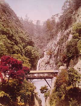 Covered bridge in a steep gorge, with waterfalls in the background, in Japan
