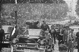 President Dwight D. Eisenhower standing in automobile, waving to crowds during a ticker tape parade...Rio de Janeiro, Brazil...1960