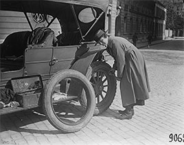 Miss Sybil Robeson of Boston, chauffeur for the American Fund for French wounded, changes tire on the road...1918