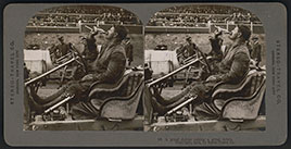 Race car driver Louis Chevrolet in his open-cockpit automobile drinking a Coca-Cola during the Atlanta National Automobile Exposition of 1909
