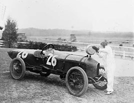 Woman putting water in radiator of Stutz Weightman Special no 26. on Benning race track...