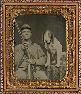 Unidentified soldier in Confederate uniform with shotgun sitting next to dog