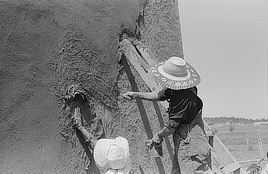 Spanish-American women plastering adobe house, Chamisal, New Mexico. Film negative by Russell Lee, 1940. Prints & Photographs Division